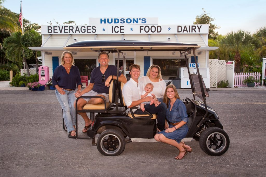 Family in a golf cart in front of Hudson's grocery store in Boca Grande