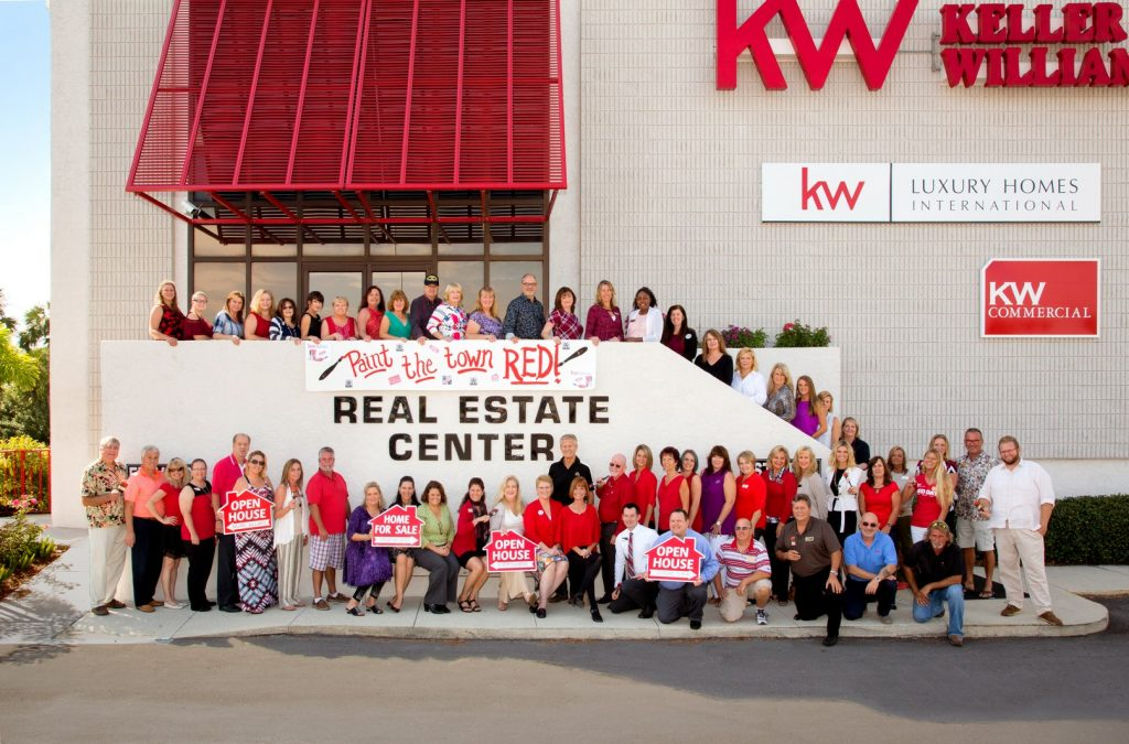 Keller Williams Real Estate Team Holding sign reading Paint the Town Red