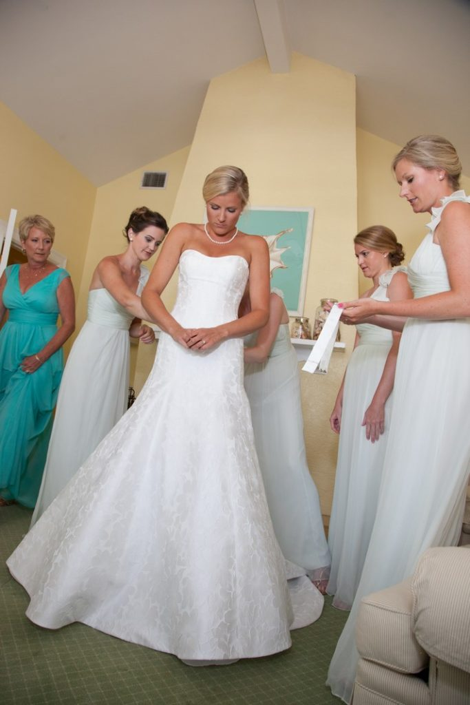 Bridesmaids helping the bride with her gown