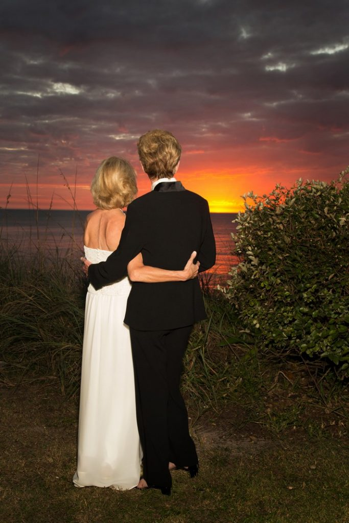 Bride and Groom Watching the Sun Setting over the Ocean