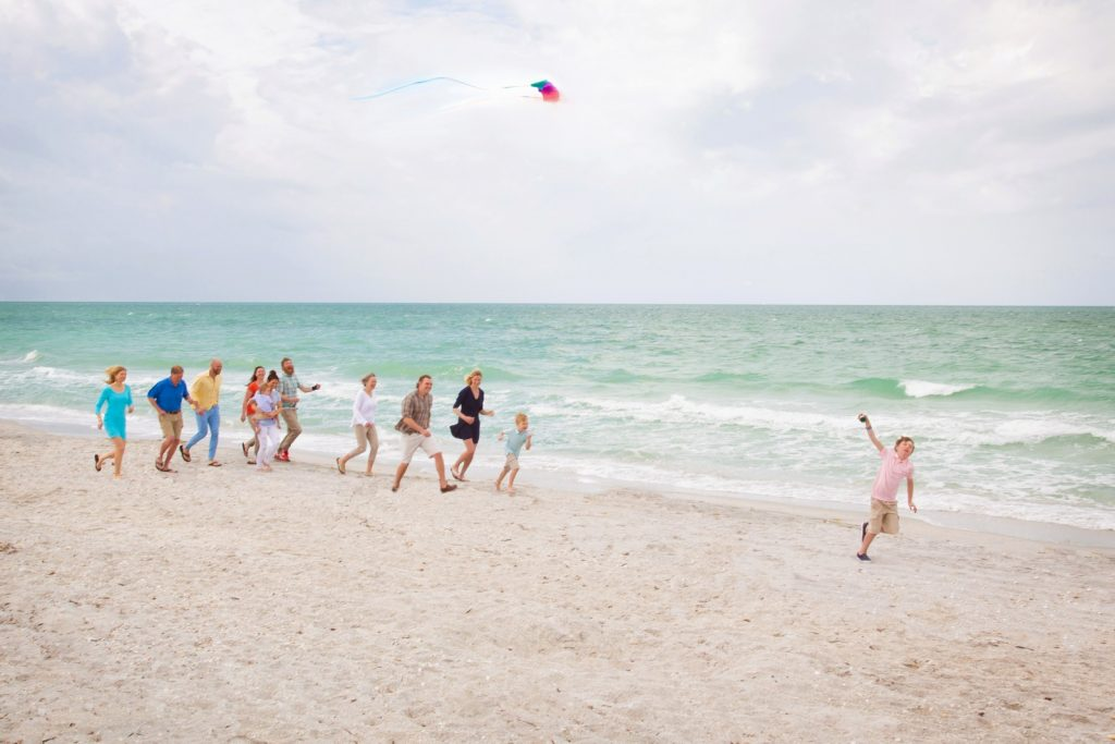Family chasing a boy flying a kite