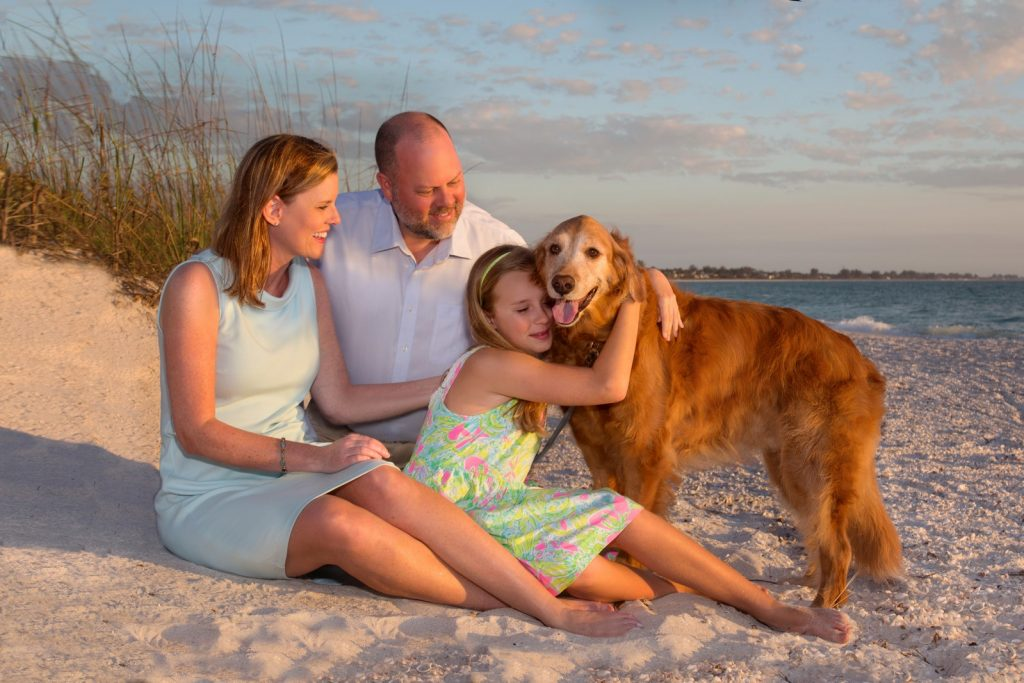 Beach portrait of a family with a golden retriever