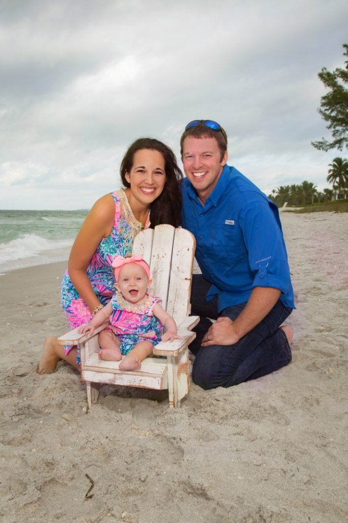 Family of three, baby seated in an Adirondack chair